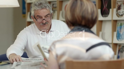 Senior man reading newspaper with wife in recreation center