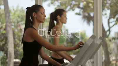 Young women working out, running on treadmill in gym