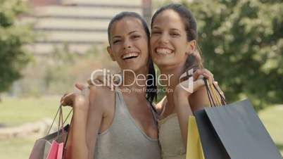 Happy young women smiling with shopping bags