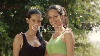 Two female friends smiling after jogging in park