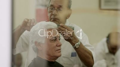 Senior man cutting hair to client in old barber shop
