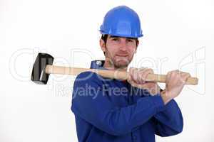 Worker carrying a mallet on his shoulder