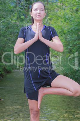 Frau macht Yoga im fließenden Gewässer