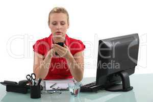 Blond receptionist typing text message