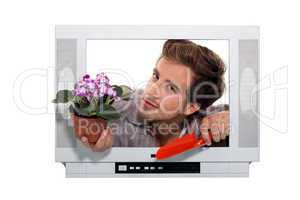 man holing flowerpot and a trowel looking through a television frame