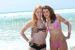 Two young women in bikinis posing in the surf