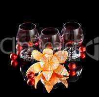 Glasses of wine, tangerine and chocolate on a black background