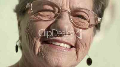 Elderly woman with glasses smiling and looking at camera