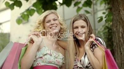 Two happy female friends smiling with shopping bags