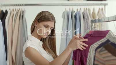 Beautiful young woman choosing shirt in clothes shop