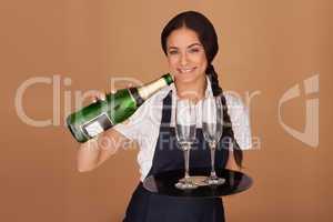 Beautiful waitress pouring champagne