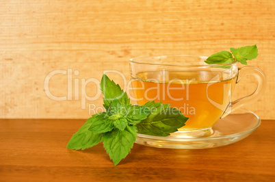 Herbal tea in a glass cup with mint on a wooden board