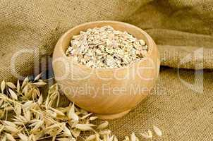 Oat flakes in a bowl on sacking