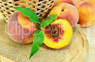Peaches with leaves and a basket on board
