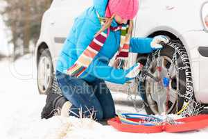Woman putting chains on car winter tires