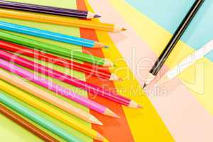 Color pencils on colorful papers close-up