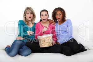 Three scared women sat on sofa watching movie