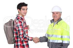 young apprentice with backpack shaking hands with senior foreman