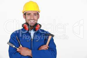 portrait of craftsman with safety helmet and earmuffs holding tools