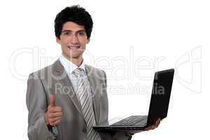 businessman holding a laptop and making a thumbs up sign