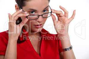 Woman putting on glasses