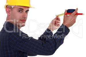 Tradesman using a measuring tape