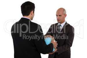 Two businessmen holding globe