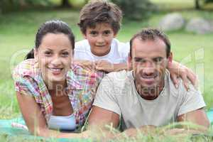 Parents and son lying on the grass