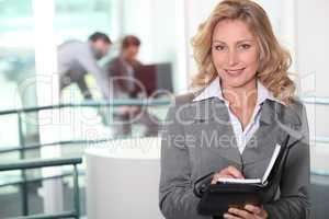 Businesswoman writing in her agenda
