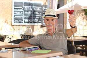 senior man toasting on a cafe terrace