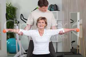 Personal trainer helping his client with her posture