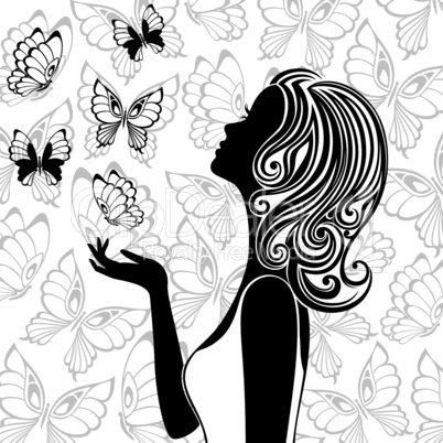 Silhouette of young woman with flying butterflies