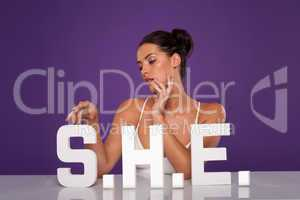 Sensual woman caressing the letters S.H.E