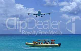 Passenger airplane overflies boat.