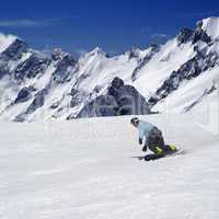 Snowboarder on ski piste in high mountains