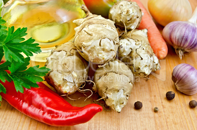 Jerusalem artichokes with vegetables and oil on board