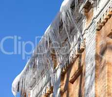Snow-covered roof with icicles