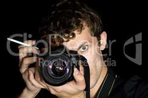 The young man - photographer behind work. Isolated on a black ba