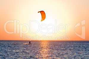 Silhouette of a kitesurfer on a gulf on a sunset
