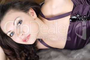 Attractive young woman lying on grey fur coat