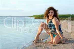 Beautiful young woman sitting on the bay