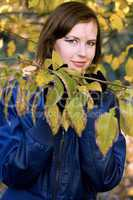 smiling girl amongst the autumn leaves