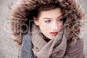 Junge Frau im winter mit kapuze und fell jacke