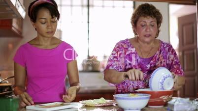 Mother daughter preparing meal together