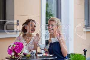 two beautiful young girls in summer outfit have lunch