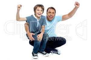 Joyous father and son cheering loud