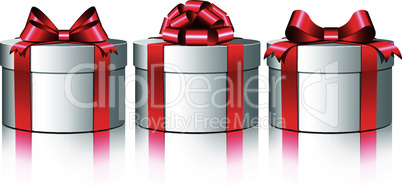 Three white gift boxes with a red bows.