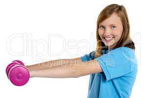 Young fit girl exercising with pink dumbbells