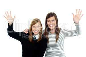 Mum and daughter waving hands at the camera