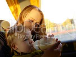 Mother is feeding her kid in the bus.